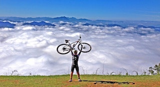 This picture shows a man with his bicycle in the top of a mountain
