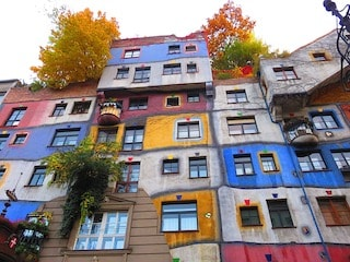 this image shows you hundertwasserghaus, a beautiful multi-colours establishment.